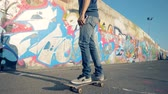 kaykay : A skateboarder rides, slow motion. Young man rides his skateboard on a road.