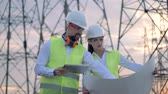 kablolar : Working professional engineers stand near power lines, close up.