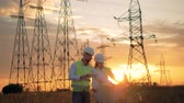 eletricista : Two engineers in uniform work near power lines. Sunset background.