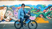 ciclismo : Young man is sitting on his BMX against the background of a graffiti wall