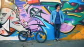 wandbild : Male teenager is standing against the graffiti wall with a bicycle