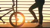 gelosia : Close up of bicycles wheel and male legs against the city background