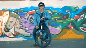 hile : Young man is sitting on his bicycle near a painted street wall