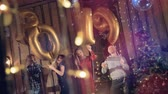 команда : Dancing people near a Christmas tree hold golden balloons making a number 2019. 2019 New Year concept.