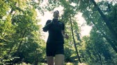 innovative technology : Young man with a futuristic bionic prosthetic arm is jogging along the forest Stock Footage