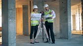 plac budowy : Construction site with two architects discussing something near land surveying equipment Wideo