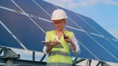talkie : An engineer works with devices, standing on a roof near solar batteries. Alternative, green energy concept.
