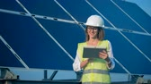solar station : Smiling female engineer architect with a tablet. Alternative, green energy concept. Stock Footage