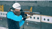 Олимпийские игры : Female athlete aims with a rifle, then looks at a camera. 4K Стоковые видеозаписи