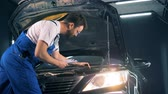 осмотр : Man works with a laptop in a garage, side view. Repairman fixing a car. Car service concept.