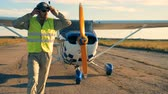 aerodynamics : Male aviator walks away from the plane and taking off the headphones Stock Footage