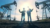 pumpjack : People stand near oil derricks on a sunset background, close up.