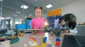 colega : Kids constructing a toy robot. Two children construct a robot in a laboratory room. Vídeos