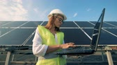 Attractive female expert is standing in front of a massive solar battery and operating a laptop Stock Footage