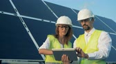 transforming : Solar engineers talking near solar panels. Green energy concept. Stock Footage