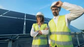 transforming : Smiling energetics engineers are standing beside a solar battery and looking into the camera. Green energy concept. Stock Footage