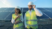 Solar installation and two inspectors standing in front of it and smiling looking into camera.