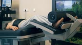 chiropractic : A woman undergoes a therapy, laying on a special machine at a clinic. 4K.