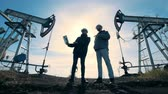 Male engineers are talking while standing between fuel pumping machines. Energy, oil, gas, fuel pumping rig. Stock Footage