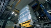 stack : Special machine wraps bottles. Bottle wrapping process at a factory.