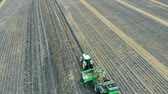 inventário : Agriculture field with a tractor collecting fresh crop of potatoes.