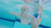 pływak : An underwater shot. A mother and a baby swimming underwater in a pool, close up. Wideo