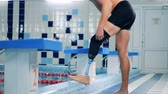 fixing : A person puts on a prosthesis at a pool, side view. Stock Footage