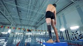 реабилитация : A handicapped swimmer warming up near a pool, back view. Стоковые видеозаписи