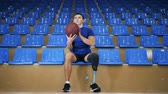 sustituto : A male with an artificial leg is playing with a basket ball while sitting Archivo de Video