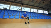 espaçoso : A man with a bionic leg is sitting with a basket ball in a spacious gym Vídeos