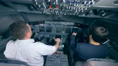 strozzare : Two pilots landing a plane in a simulator, back view. Filmati Stock
