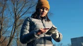 робот : A woman with a synthetic hand is browsing her mobile phone outdoors