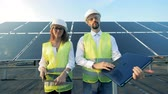 solar energy : People with gadgets stand on solar panels background, close up.