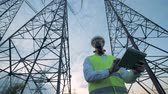 technician : Tall electricity towers and a male technician working beside them Stock Footage