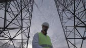 eletricista : Cloudy sky and a male technician working between tall ETL towers