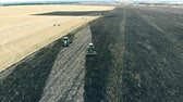 potato harvest : Combines are ploughing and harvesting a massive agricultural field field. Stock Footage