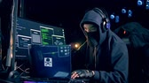 fraude : Male hacker in a hoodie is operating computers Stock Footage