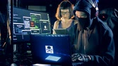 krást : Male and female hackers are working together in a computer room