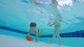 amateur : Kids mother helps him to get a toy from the bottom of the swimming pool