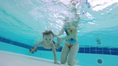 physiotherapy : Woman helps a baby to dive underwater