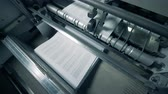 newspaper stack : Top view of printed pages getting released by the factory machine Stock Footage