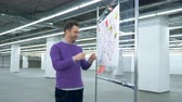 observar : Male architect is observing layouts on a plastic board with a smile