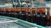 malz : Sealed beer bottles going on a conveyor, close up.