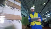 distribution automatique : Male worker is inspecting wrapping process of plastic canisters