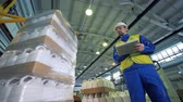 distribution automatique : A supervisor is observing plastic containers getting wrapped into cellophane