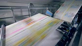 copiadora : Long sheets of newspaper on a print office line, close up.