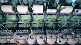 szövés : Textile plant equipment works with sewing spools with white threads.