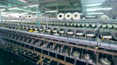 konular : Rows of spools, spinning on textile factory machines.