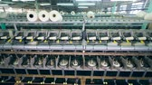 konular : Factory equipment spools white threads on big clews in a facility.