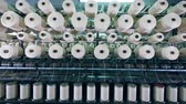 szövés : Modern textile factory machine works with spools with white fiber.
